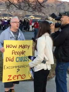 Representatives of Channel 2 news interview a participant in John Dehlin's vigil.
